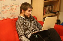 Richard Symonds on a red sofa, reading Wikipedia on his laptop