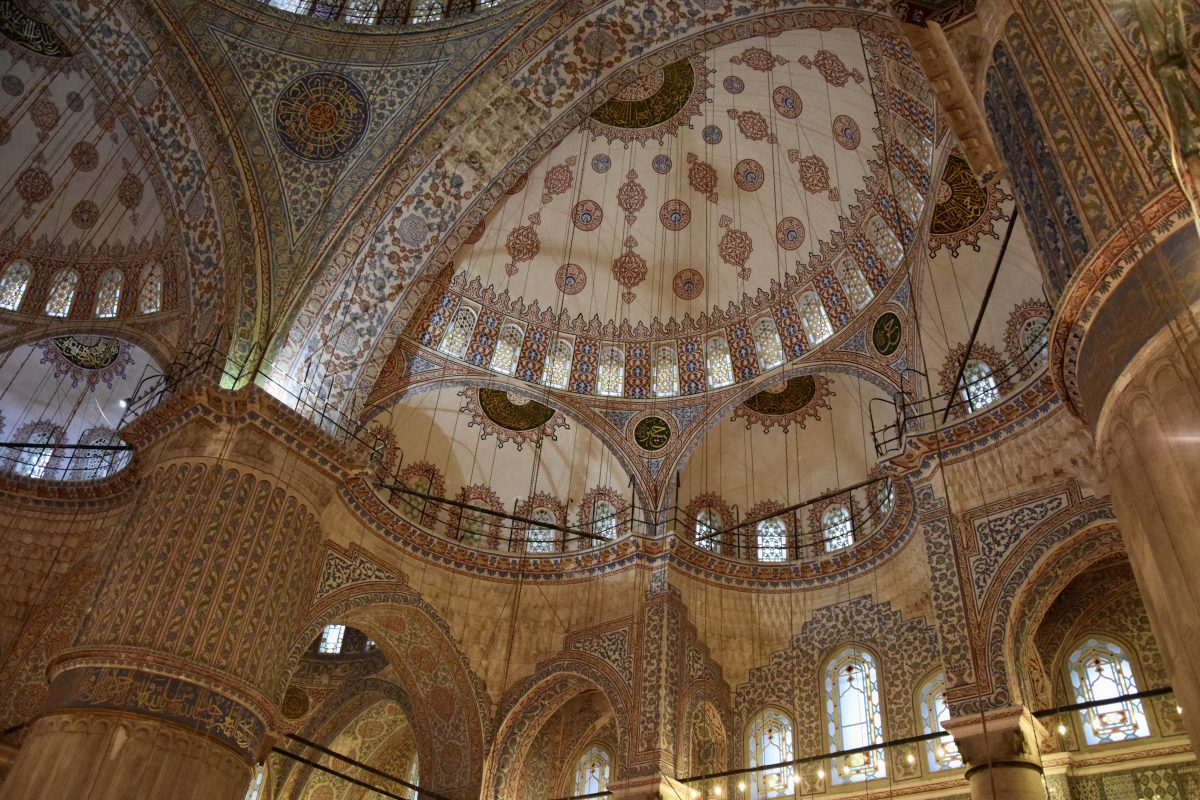 A view upwards towards the domes of a mosque, taking in all the intricate artistic details.